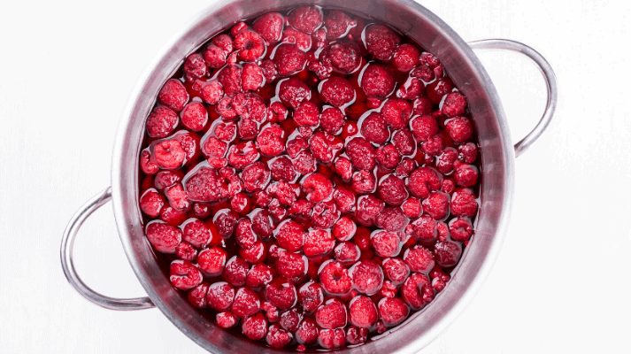 A pot of ruby red raspberries starting to cook in a large pot on the stove for delicious raspberry rhubarb jam