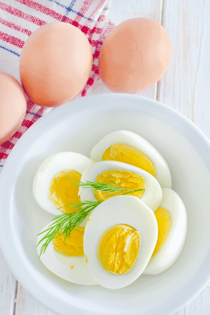 Hard-boiled eggs that were cooked in the instant pot sliced in half, sitting on a white plate, with 3 farm-fresh brown eggs sitting outside the plat