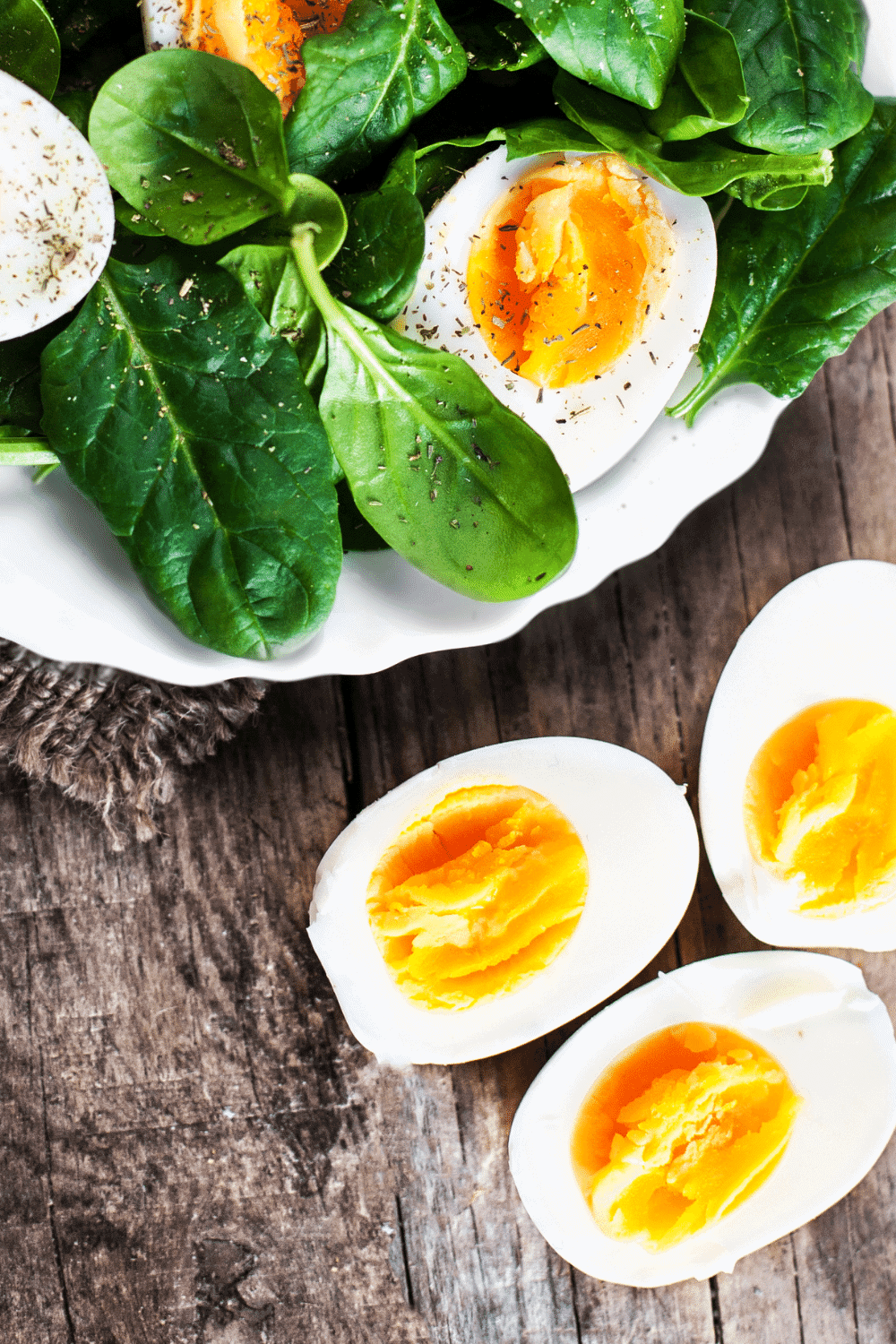Hard-boiled eggs cooked in the instant pot, served with a spinach salad, sprinkled with salt and pepper
