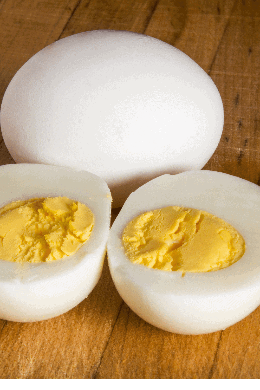 Instant Pot hard-boiled eggs after they are cooked, with one egg whole and one egg sliced in half