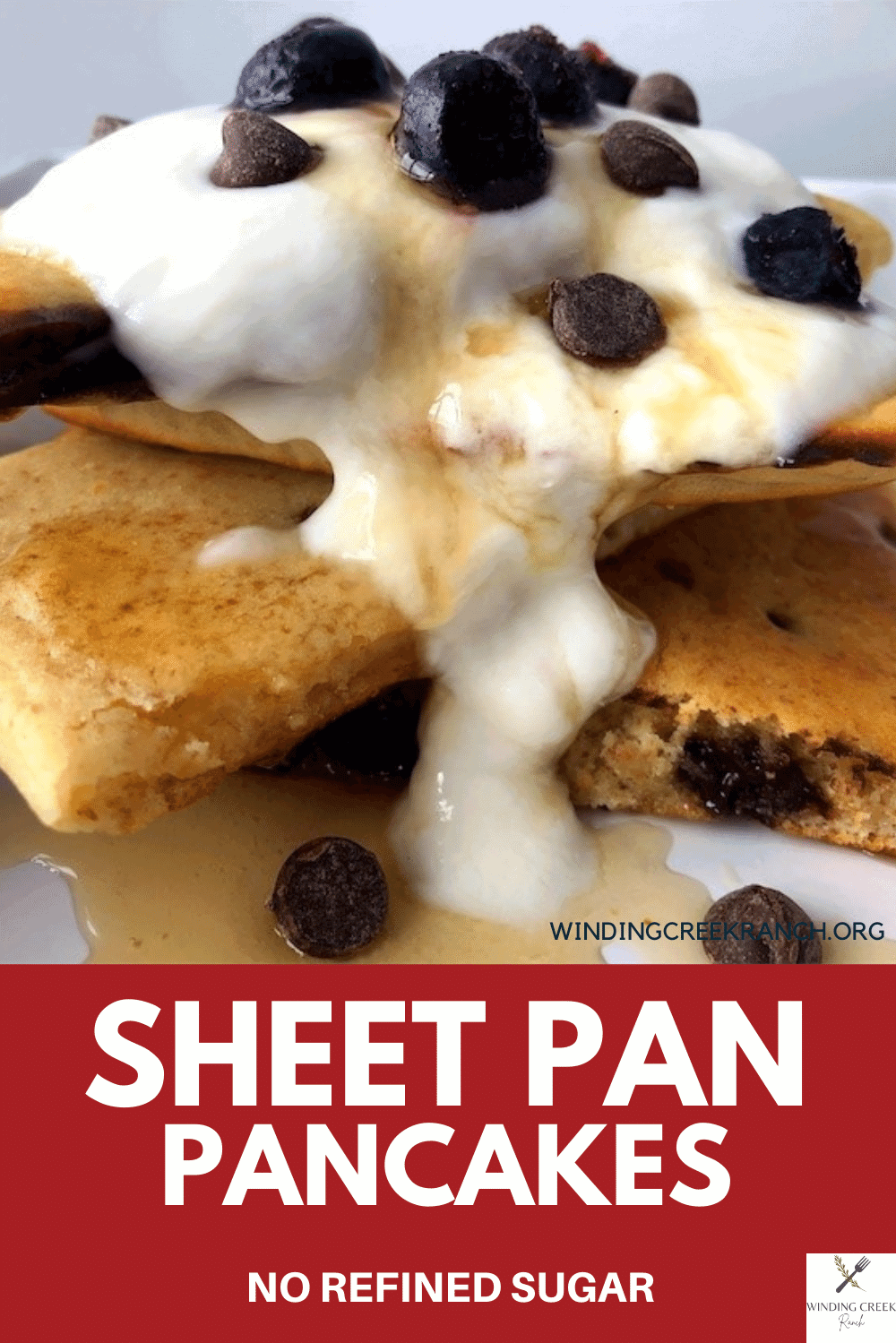 Pinterest image for easy to make sheet pan pancakes covered in whip cream with blueberries and chocolate chips and maple syrup on top