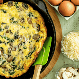 Spinach and Mushroom Omelet with onion and shredded cheese cooked in a cast iron pan being flipped over with a rubber spatula