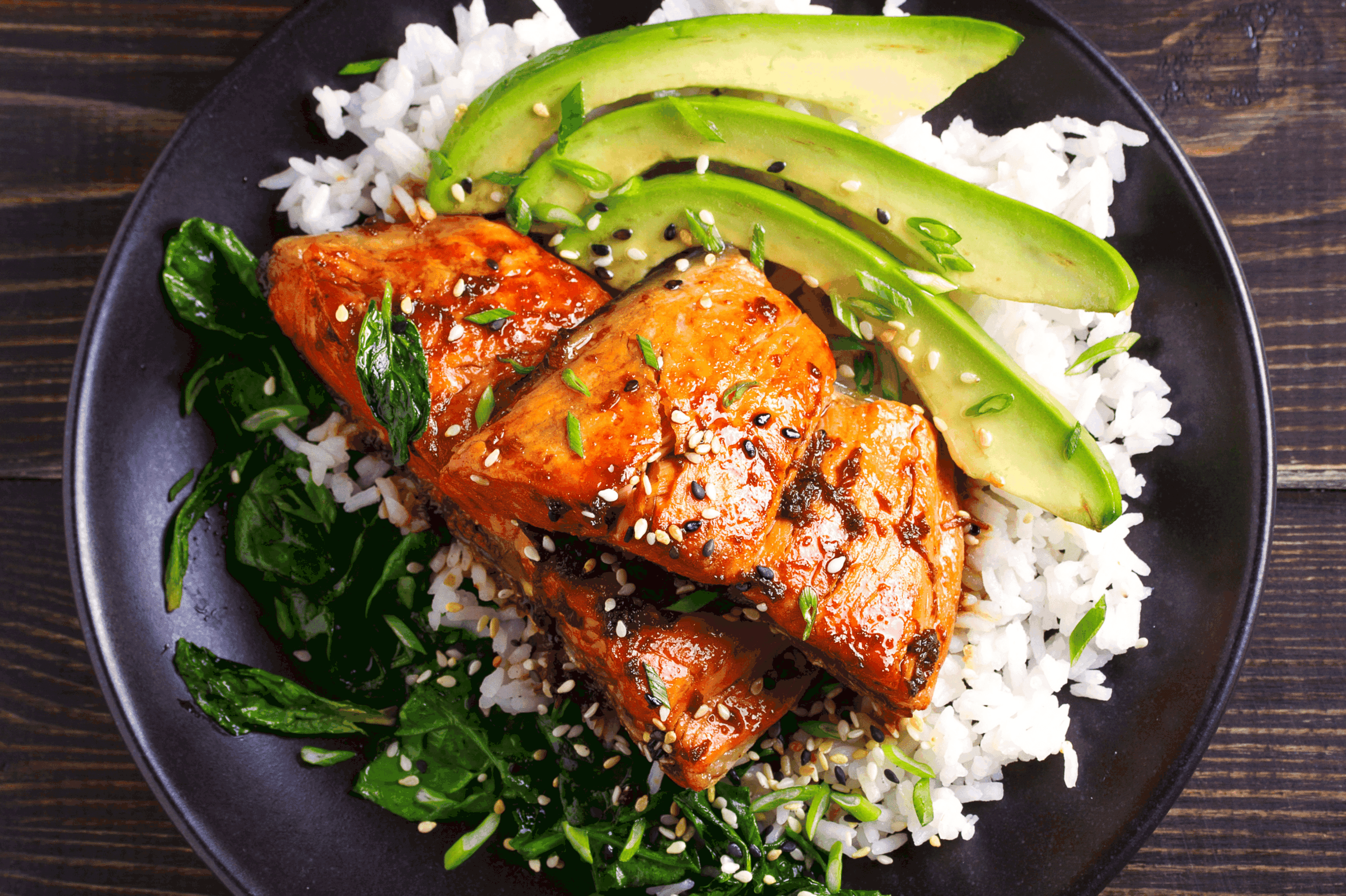 Maple-Soy Glaze Salmon served over a bed of rice with sliced avocado and cooked spinach
