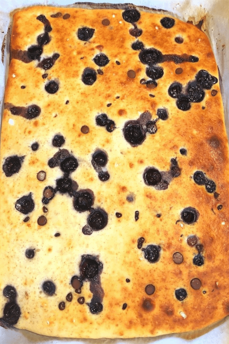 Homemade buttermilk sheet pan pancakes with blueberries and chocolate chips just taken out of the oven, nicely browned on top.