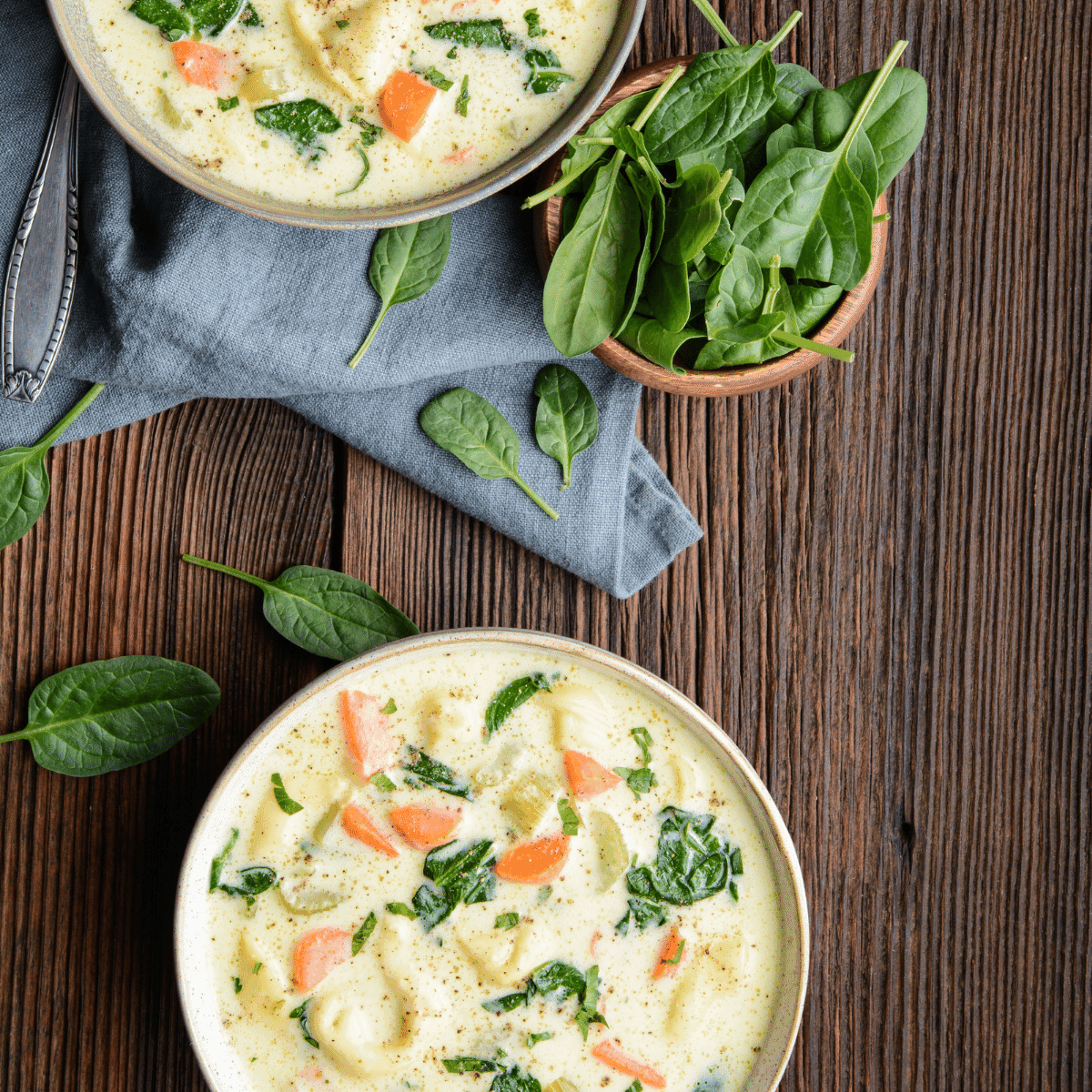Two bowls of creamy chicken pasta soup with spinach and carrots, with a bowl of fresh spinach on the table with a blue napkin