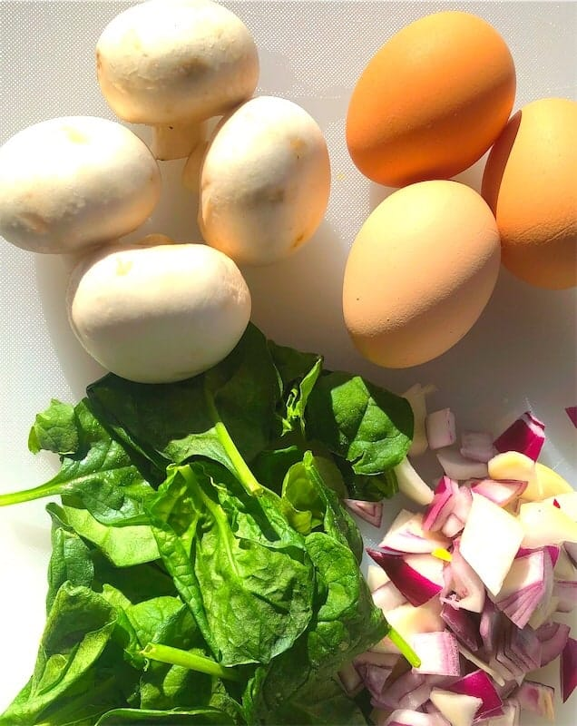 Ingredients for the omelet include fresh mushrooms, green leafy spinach, red onion, and farm fresh eggs
