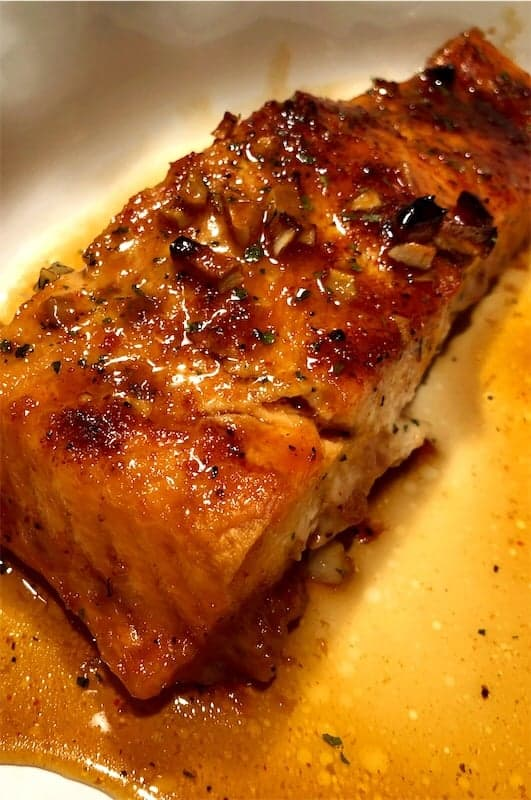 A fillet of delicious and nutritious maple-soy glazed salmon with the glaze spooned over top of the salmon