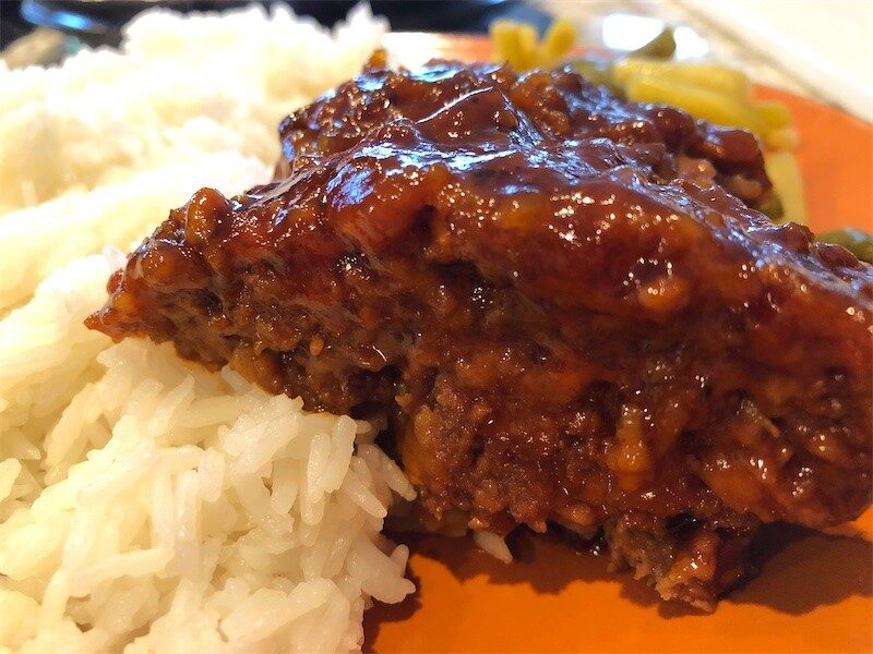 A slice of delicious homemade meatloaf served on a plate with jasmine rice and green beans and yellow beans