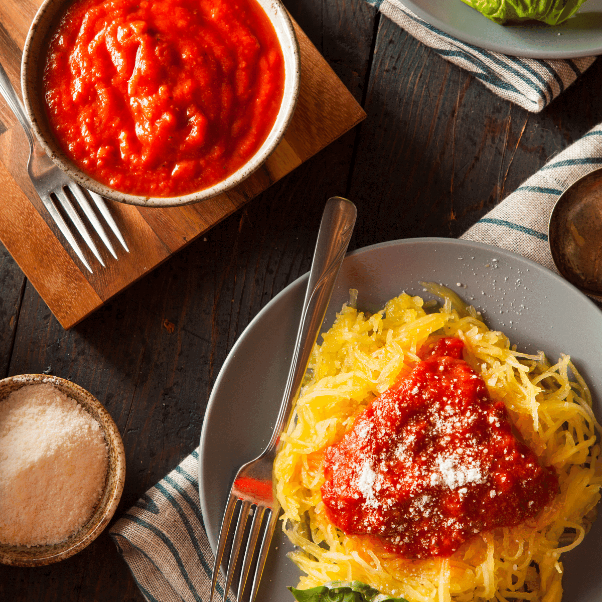 A plate full of delicious spaghetti squash noodles topped with parmesan cheese after it was cooked in the instant pot in only 8 minutes
