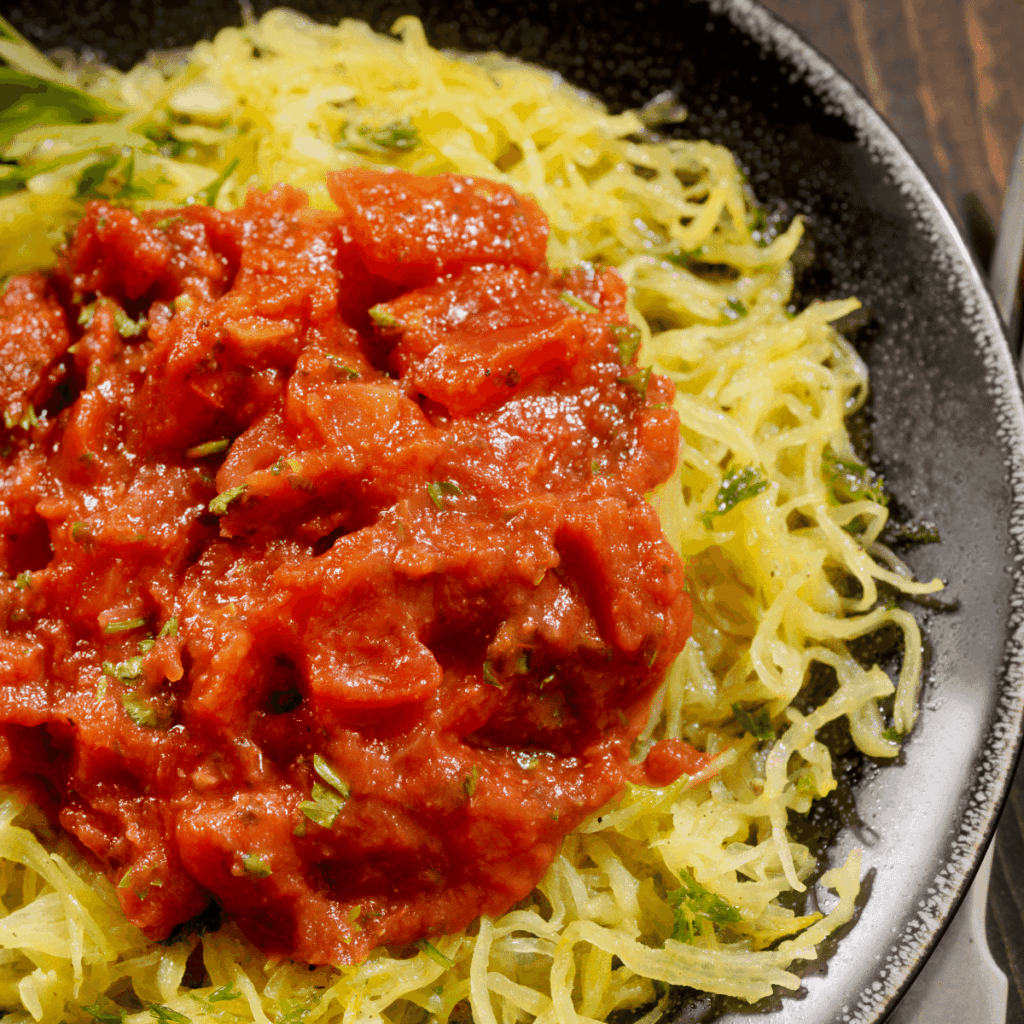 A plate of spaghetti squash topped with marinara sauce on a plate