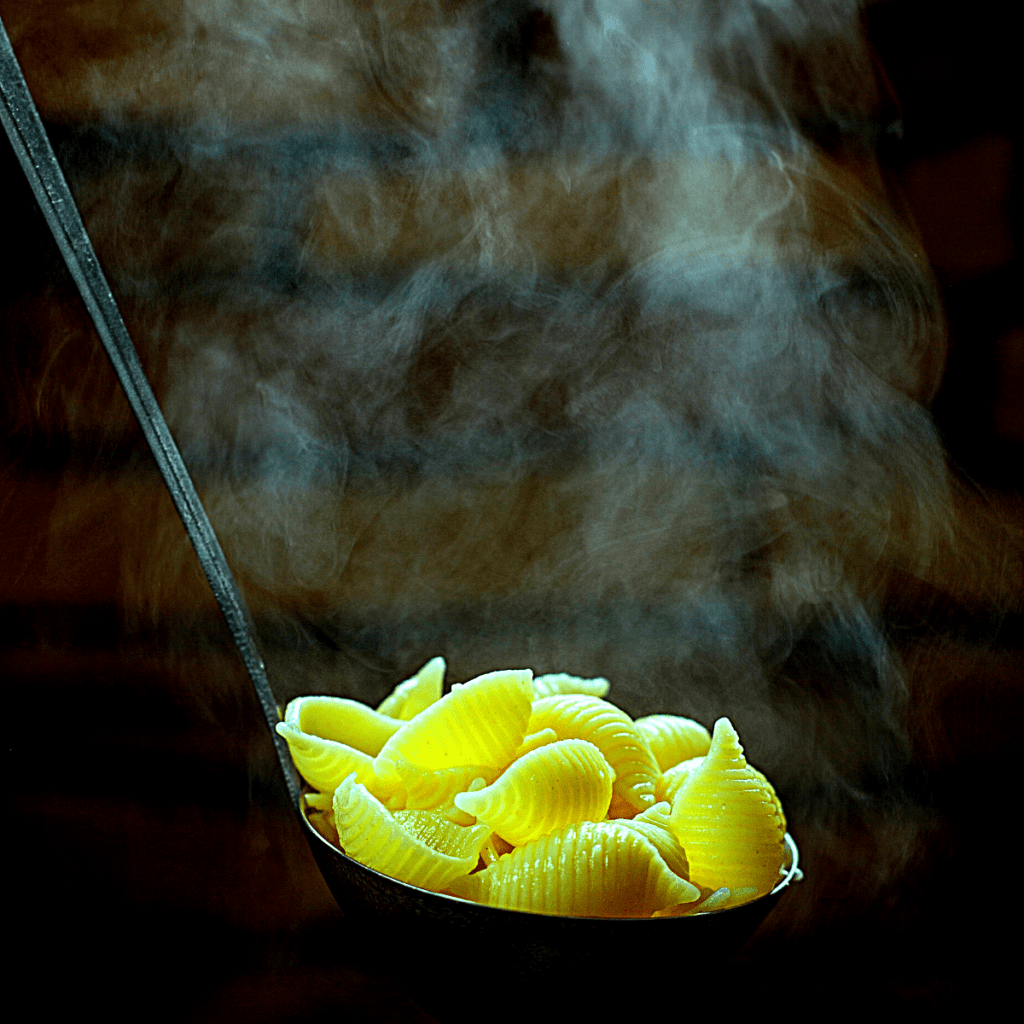 Place pasta shells into soup using a ladle and mix well