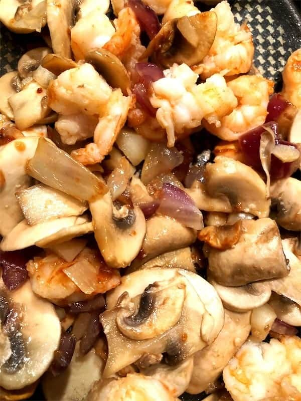 mushrooms sauteed with shrimp and onions and garlic in a frying pan