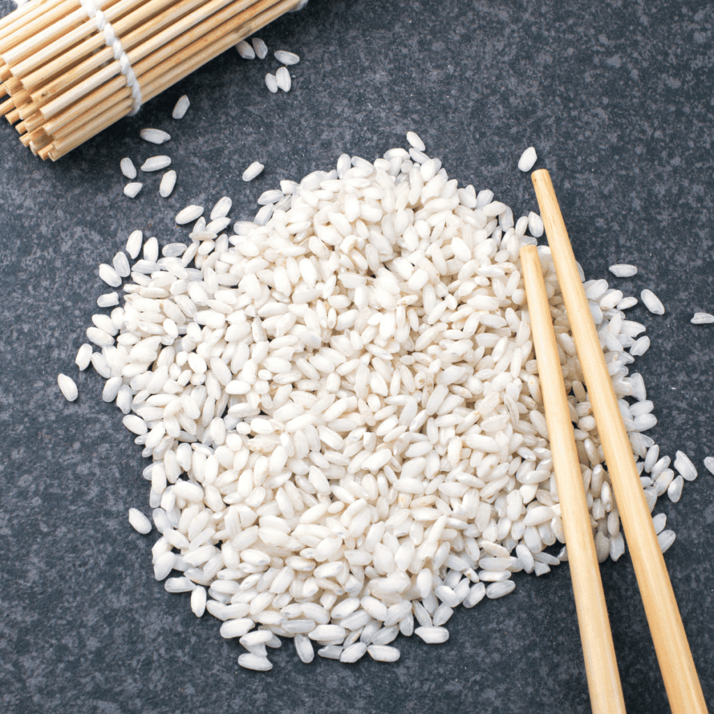Sushi rice grains on the counter with chopsticks and a sushi rolling mat in the background