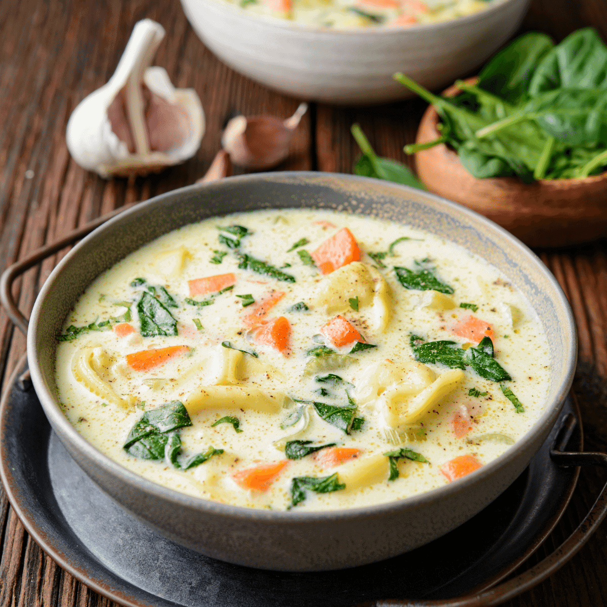 Two bowls of creamy chicken slow cooker soup with spinach and carrots and garlic