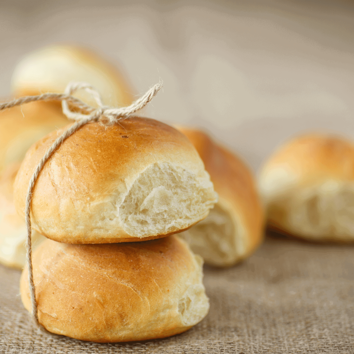 Fresh homemade dinner rolls stacked on top of each other and tied with a string