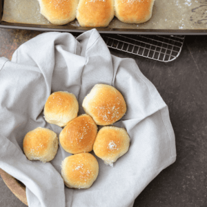 Fresh and easy to make dinner rolls in a bowl with a blue napkin and a cooling rack
