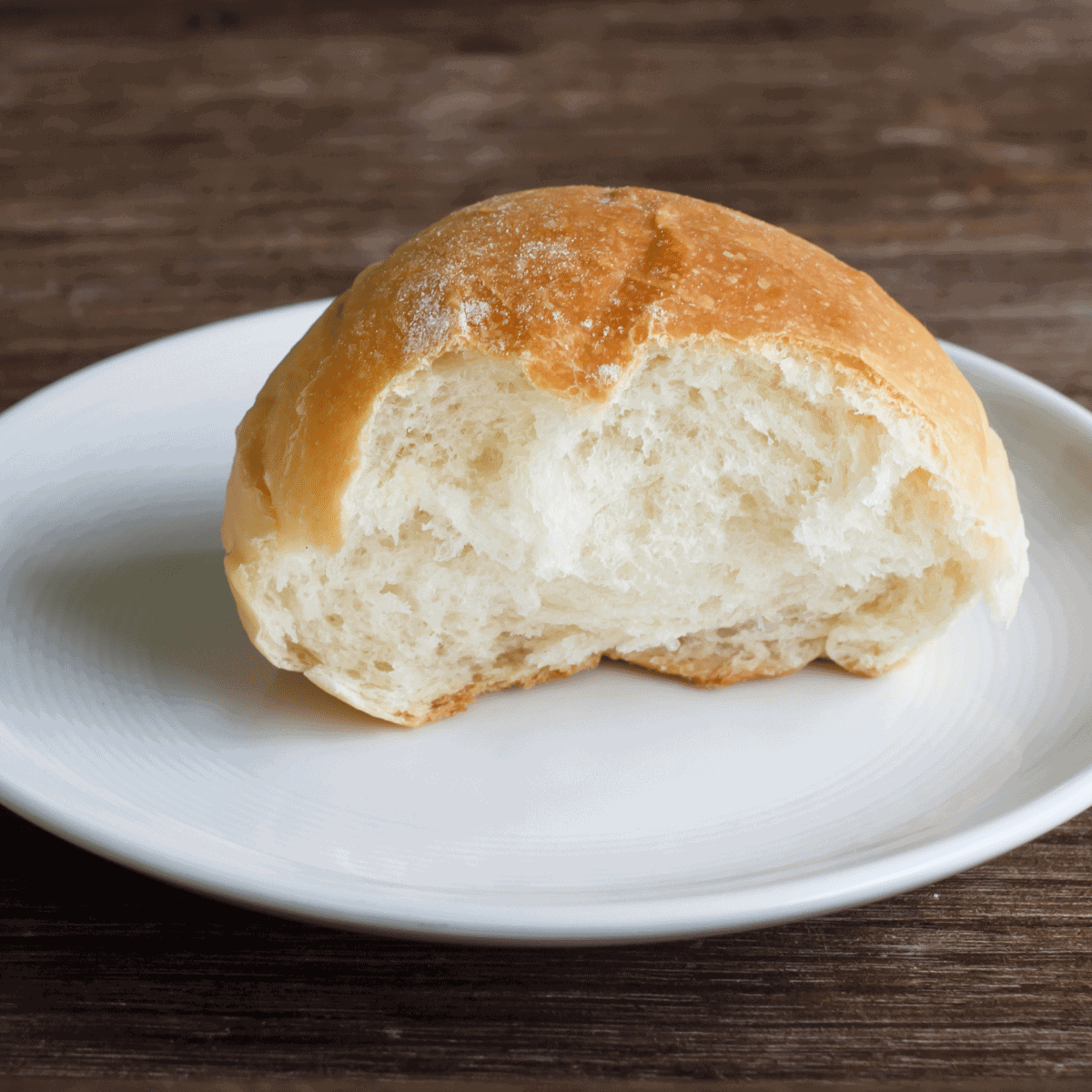 A fresh homemade dinner bun that is so soft and tender that is torn in half, on a white dinner plate