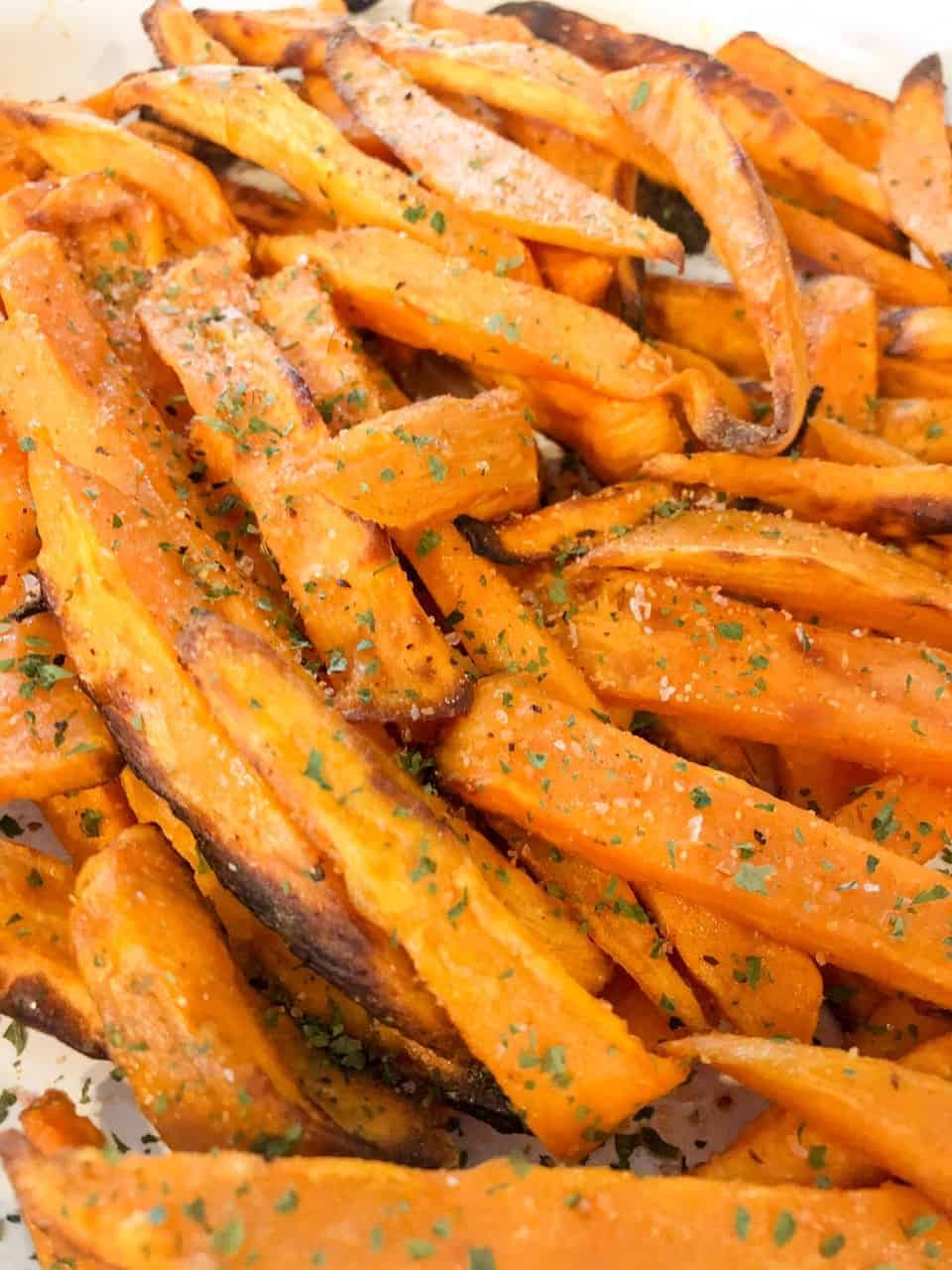 Crispy sweet potato fries topped with sea salt and parsley