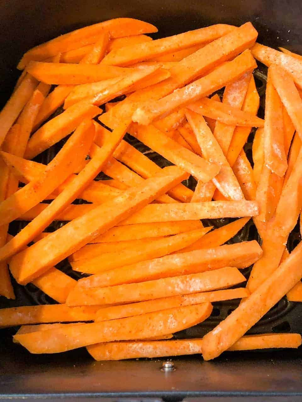 Sweet potato fries in the basket of an air fryer