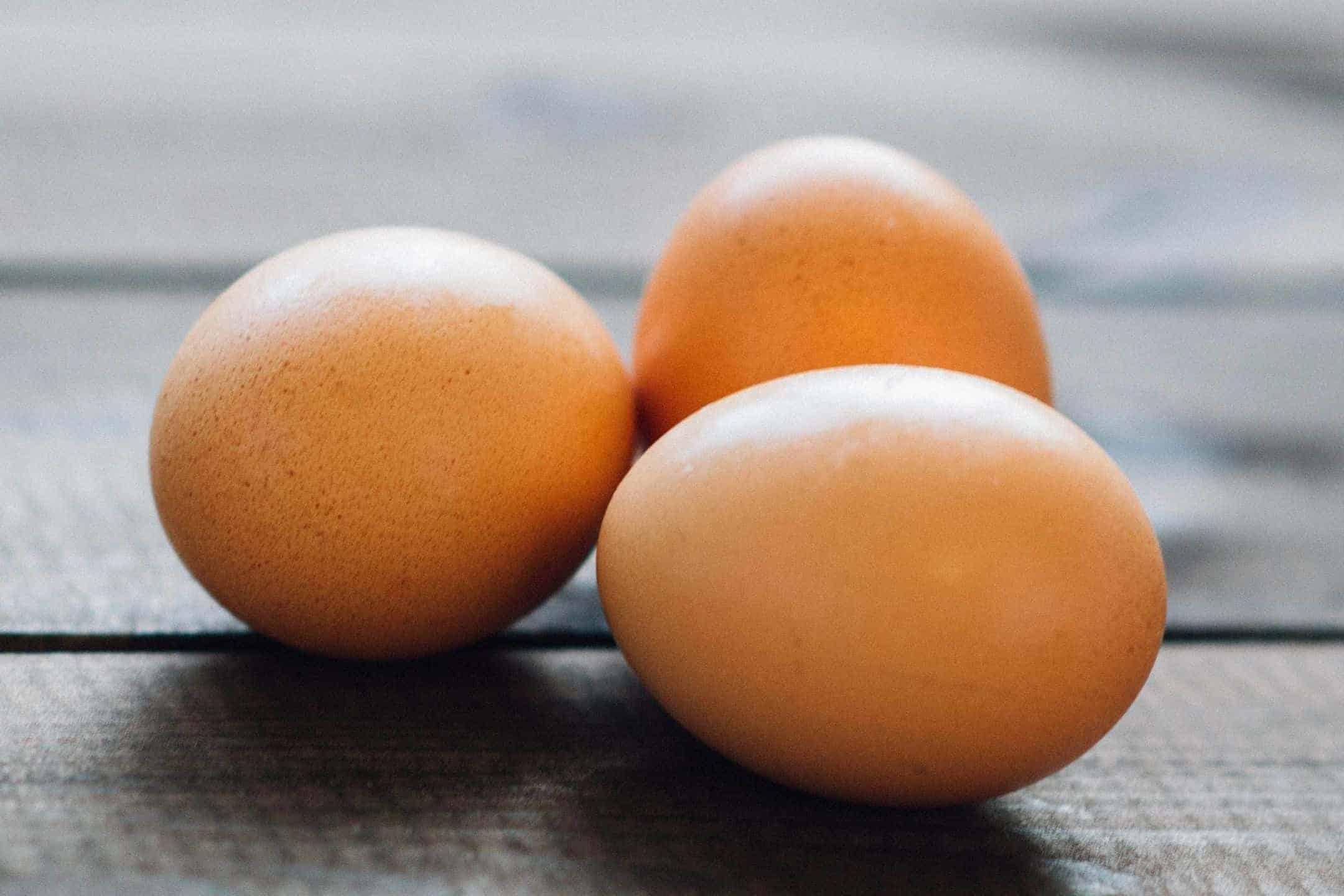 Three Farm fresh brown eggs on a picnic table