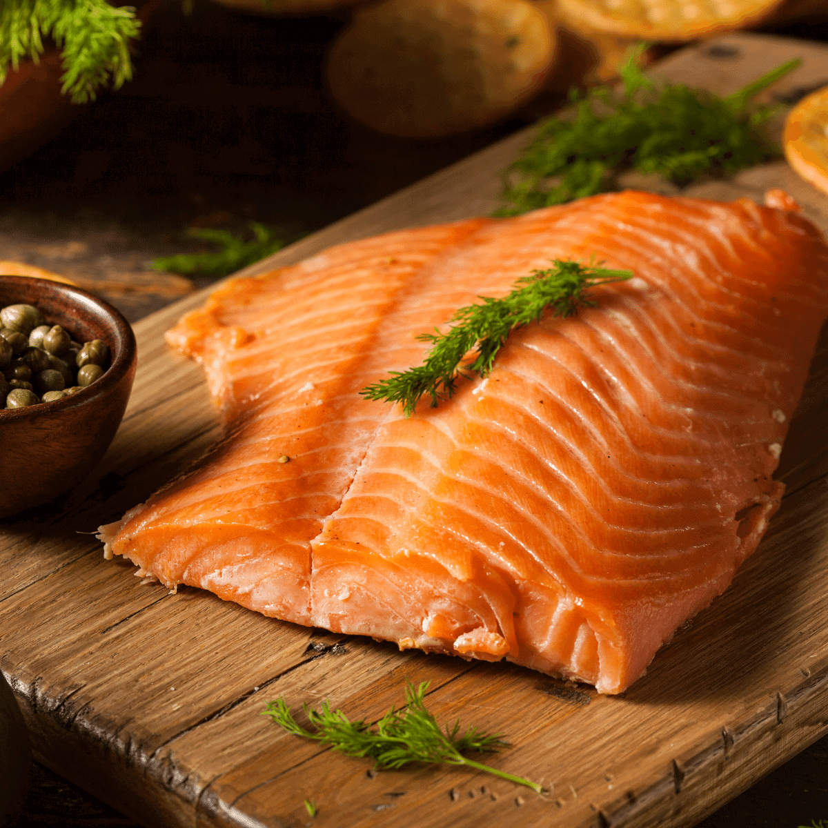 A large fillet of salmon on a wood plank
