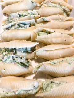 Baking pan full of stuffed jumbo shells with chicken, broccoli, and spinach