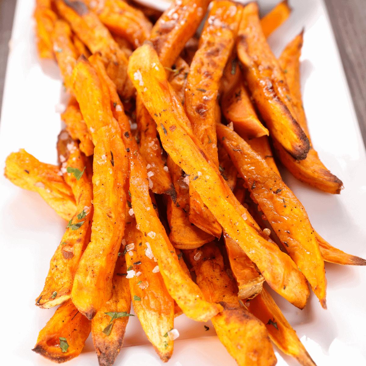 ultra crispy sweet potato fries on a white plate sprinkled with sea salt