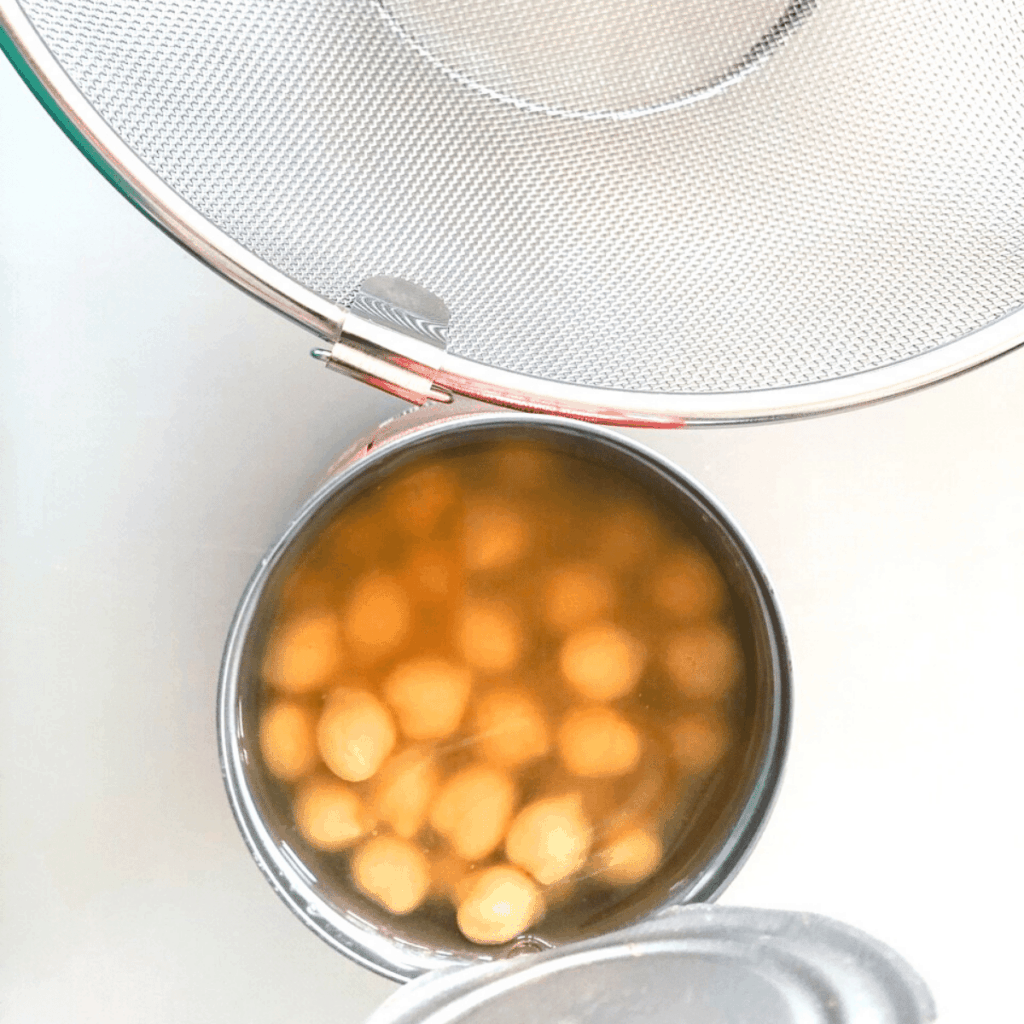 A can of chickpeas opened and sitting beside a mesh strainer