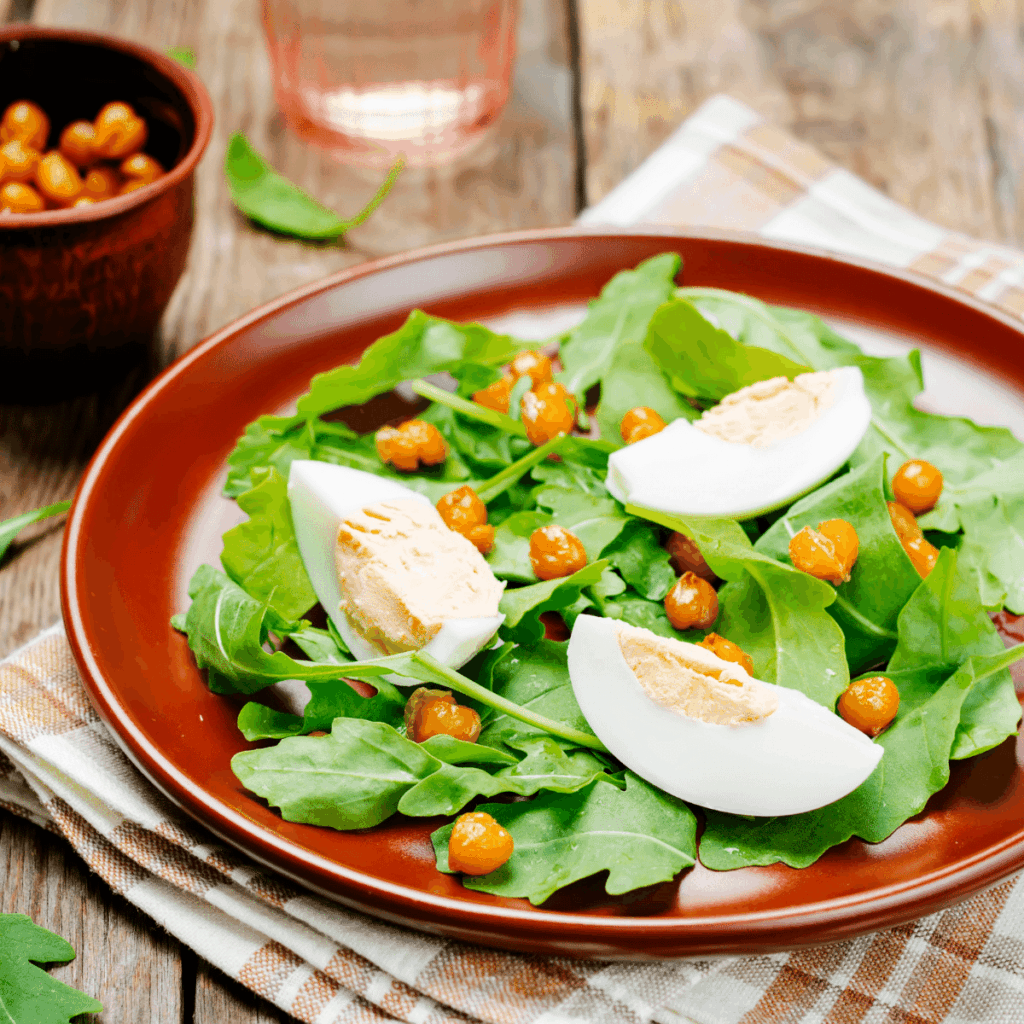 A green salad on a plate with hard-boiled eggs and chickpeas on top