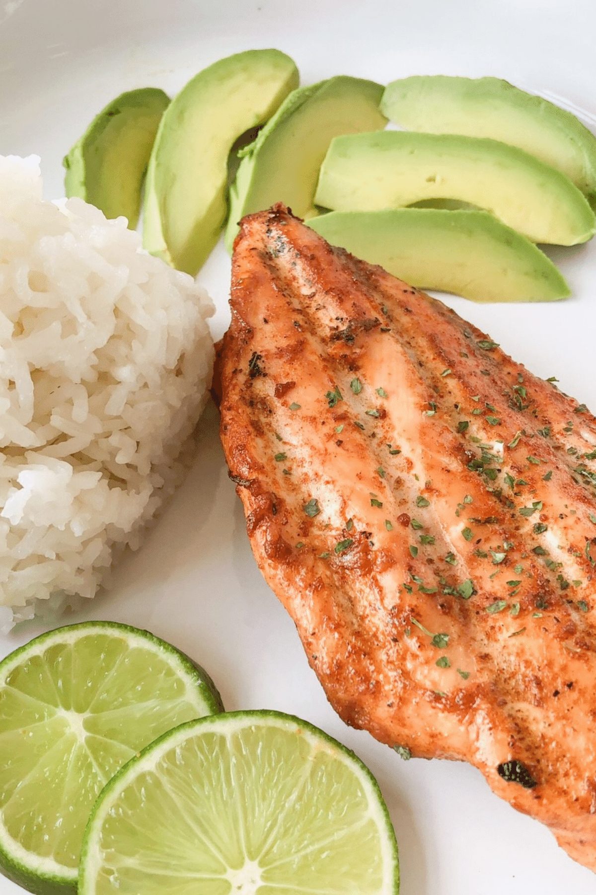 chicken breast served with white rice and avacado and lime slices