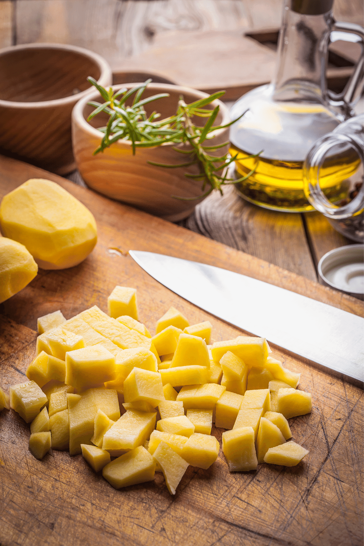 Peeled and diced potatoes on a cutting board with fresh spices and oil