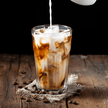 Homemade iced coffee with cream being added to the glass