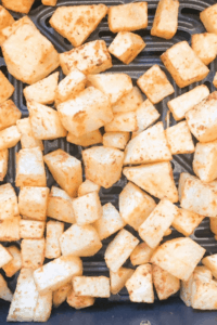 Diced potatoes in the basket of the fryer