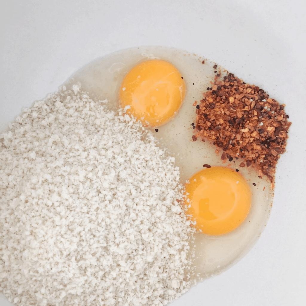 In a bowl add 2 eggs, hamburger seasoning, and breadcrumbs