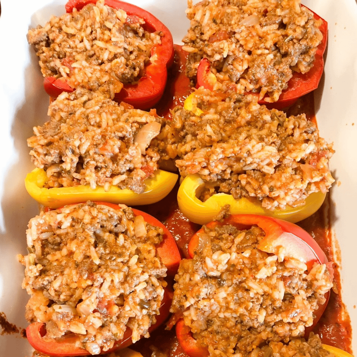 Peppers with stuffing placed in a baking dish