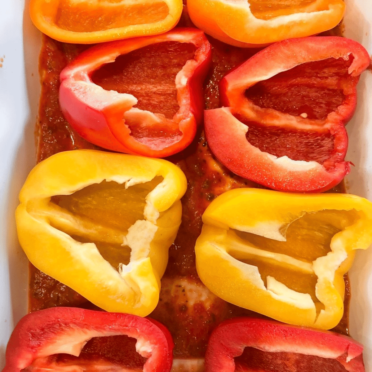 fresh peppers sliced in half and placed in a baking dish