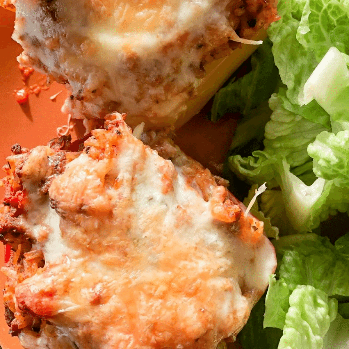 Baked stuffed peppers served with a side of crisp green salad