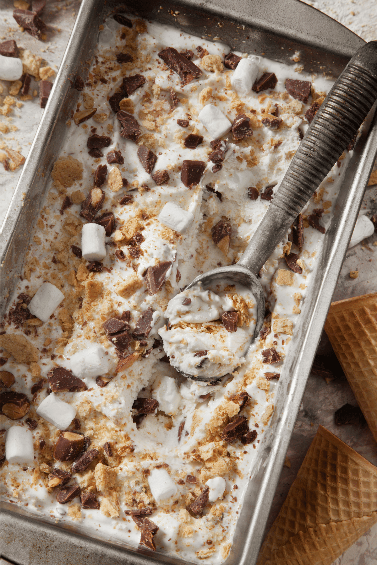 S'mores ice cream in a baking tray with an ice cream scooper and marshmallows and graham crackers sprinkled on top