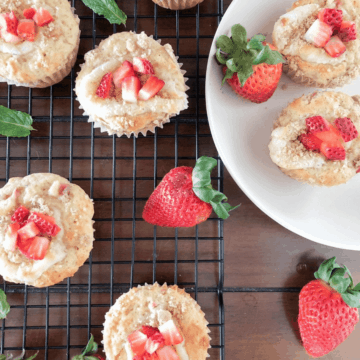Strawberry rhubarb muffins with cream cheese on a cooling rack and on a white bowl, with strawberries scattered around