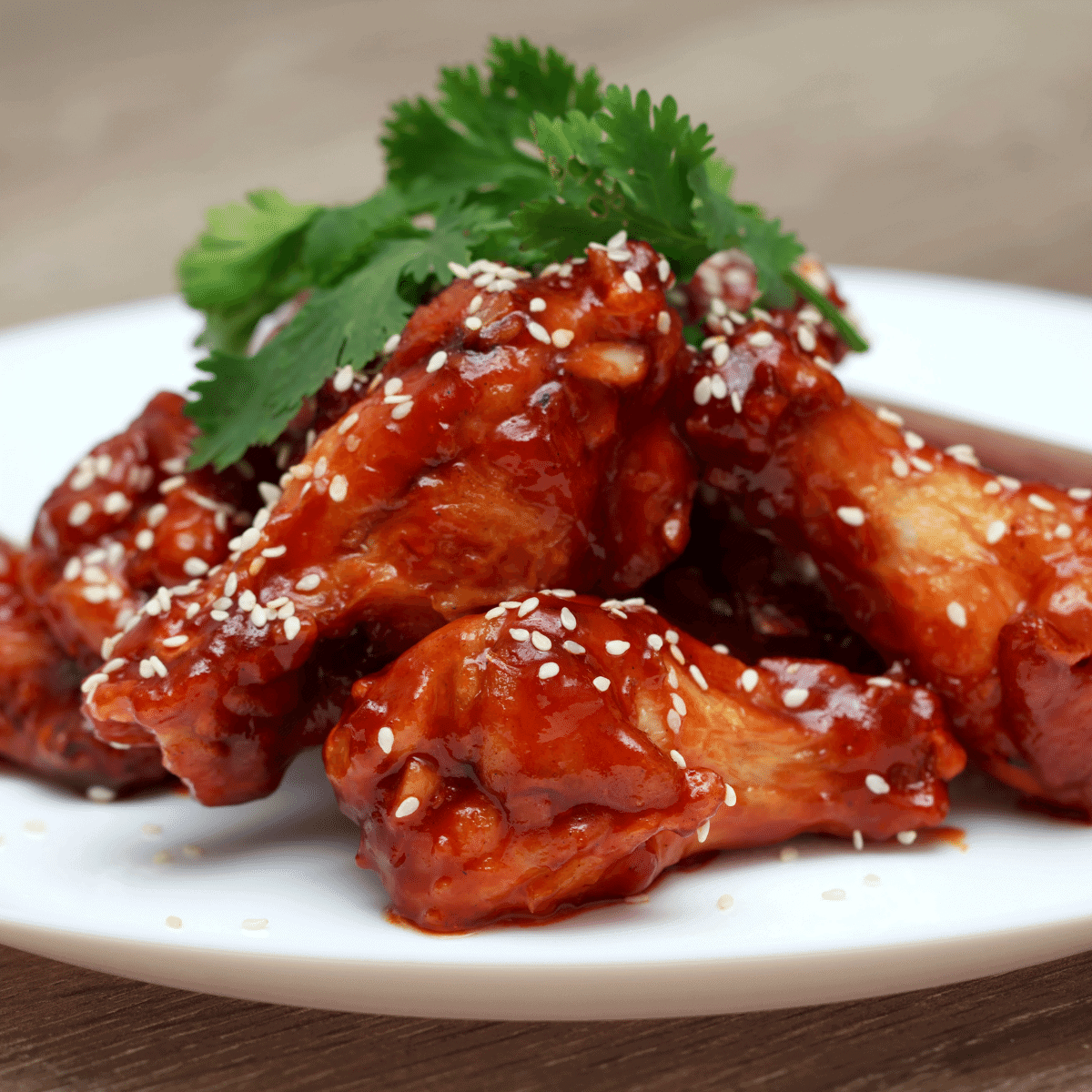 Teriyaki chicken wings served on a white plate with sesame seeds sprinkled on top