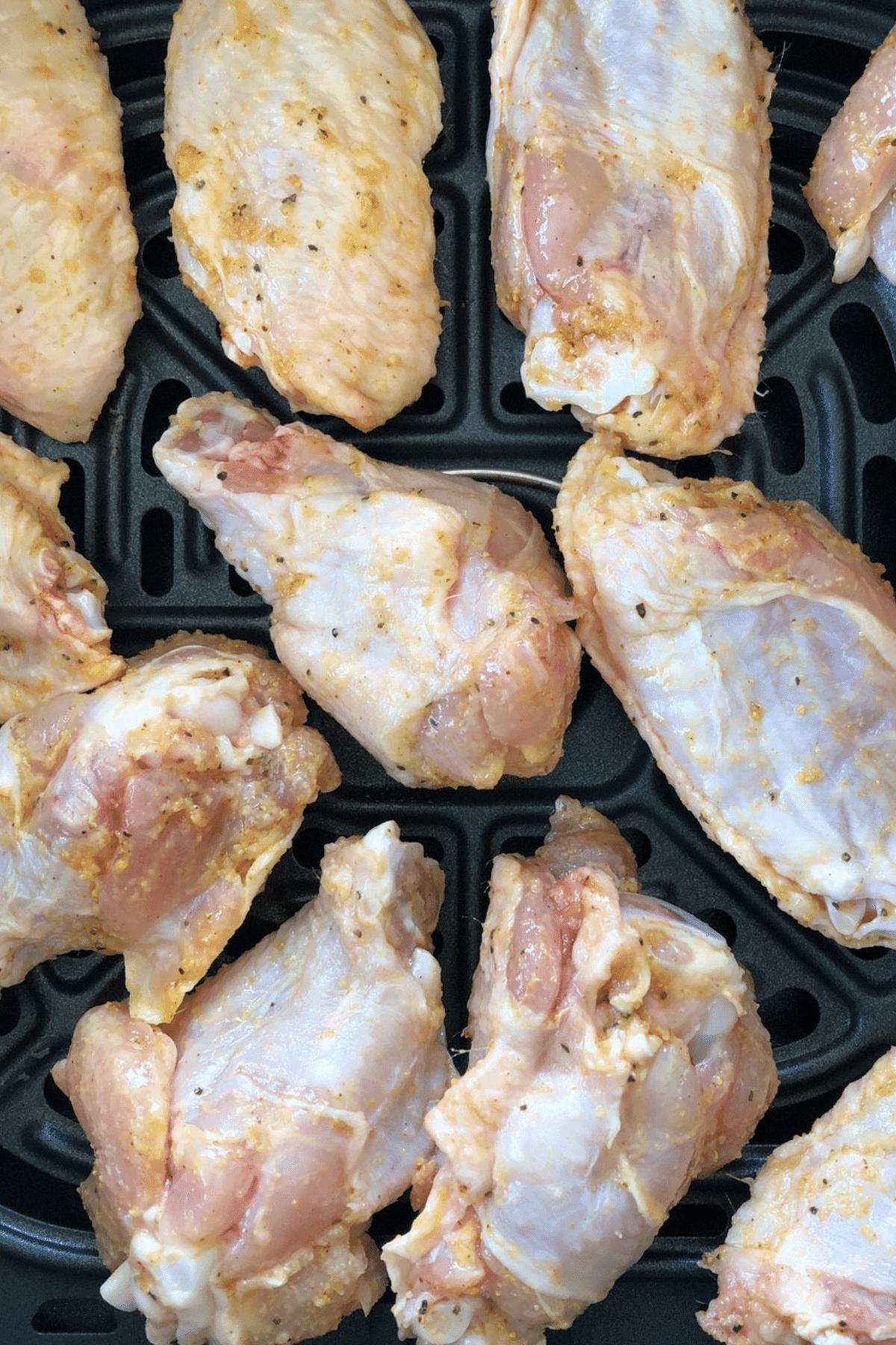 Seasoned chicken wings place in air fryer basket
