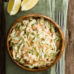 Creamy classic coleslaw in a wooden bowl with a sliced lemon on the side