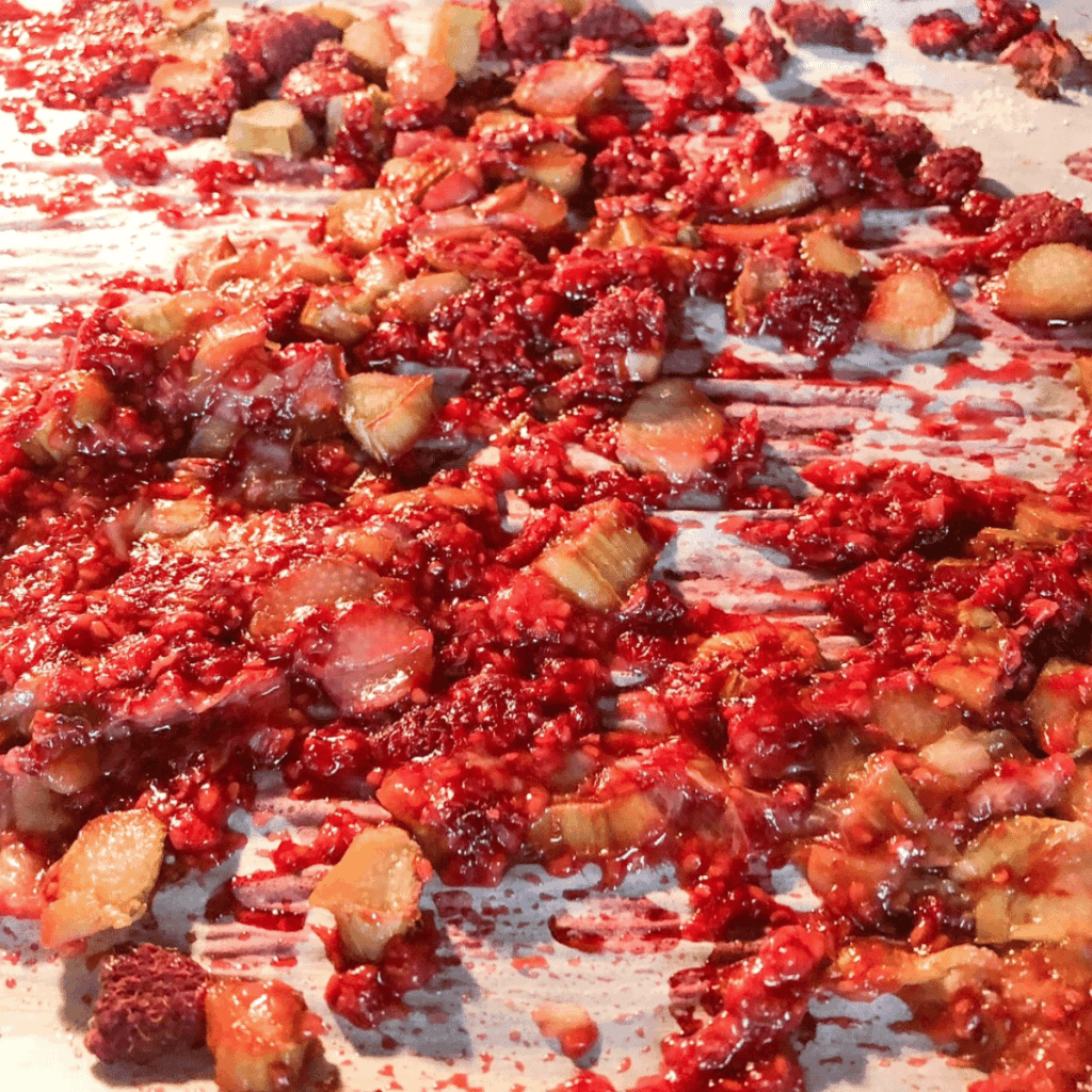 Cooked rhubarb and raspberries on parchment paper on cookie sheet