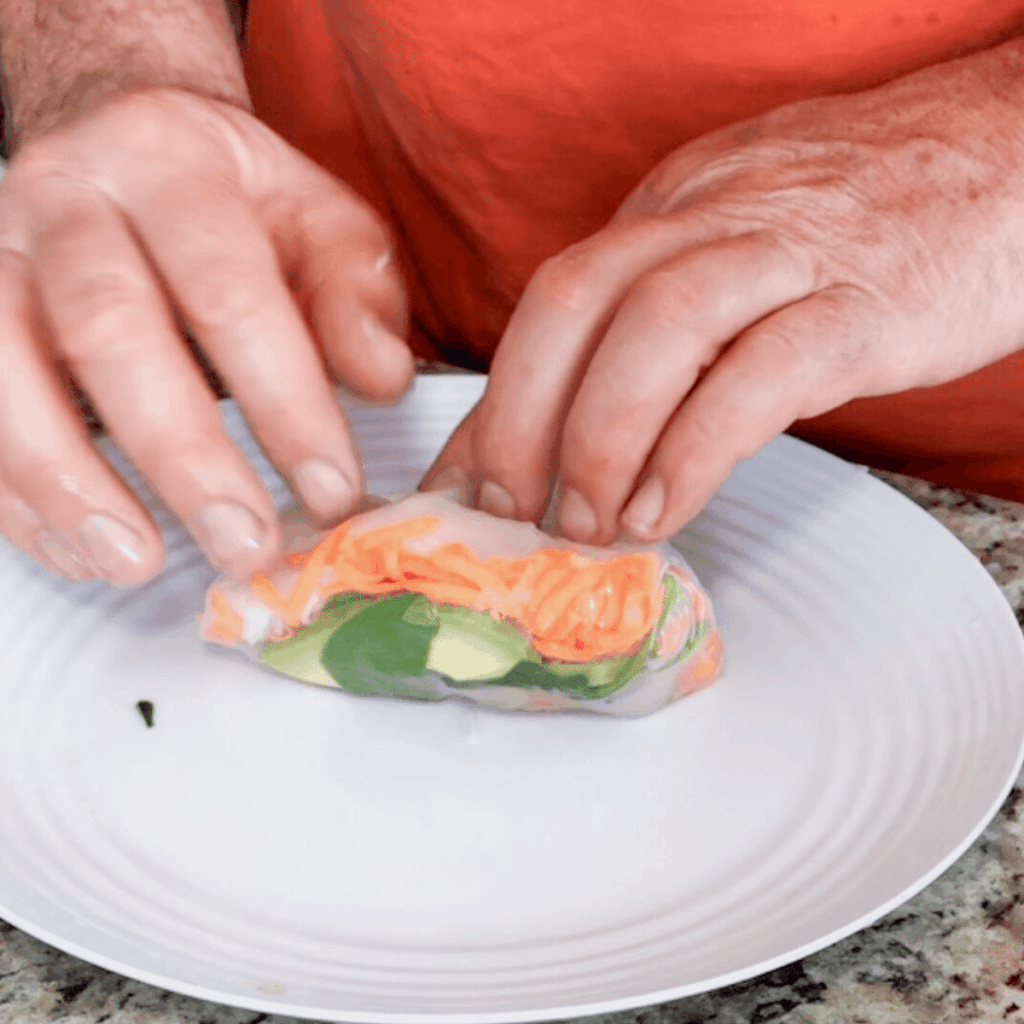 Pull the top of the rice paper down over the veggies to neatly tuck everything inside