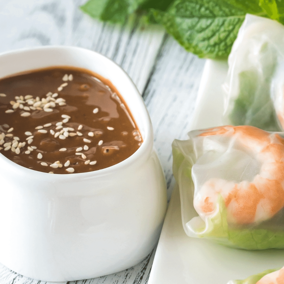 Freshly made hoisin-peanut sauce with sesame seeds on top served with a shrimp spring roll