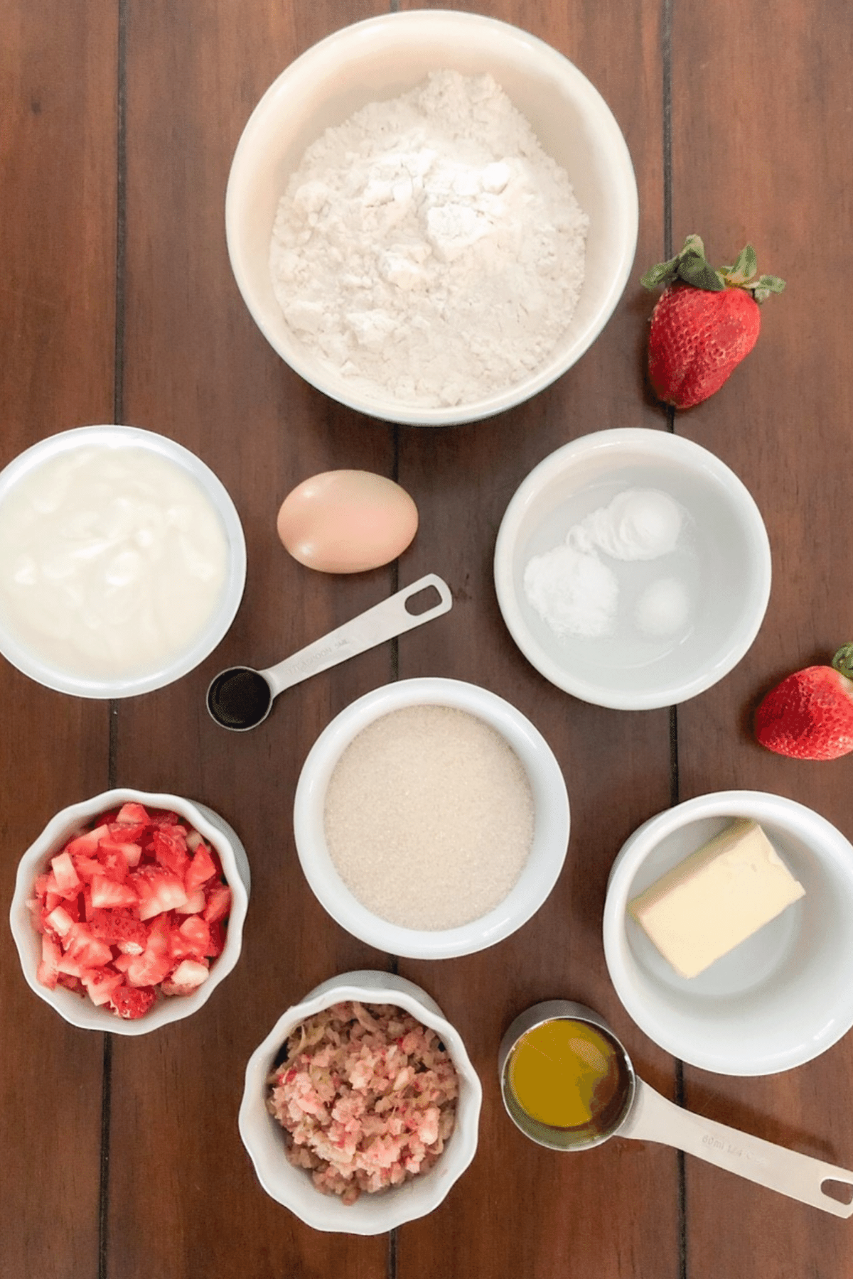 Ingredients for strawberry rhubarb muffins in measuring cups on a table