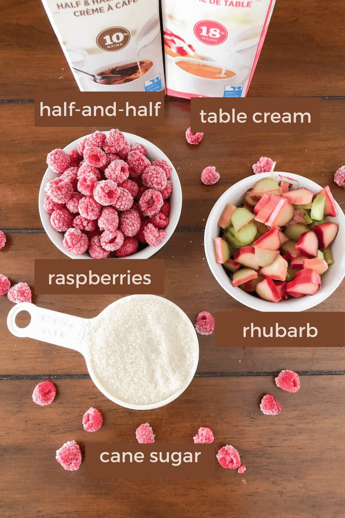 Ingredients needed to make raspberry rhubarb ice cream on a wood table