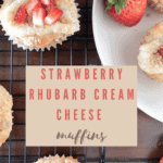 Long pin for strawberry rhubarb muffins on a cooling rack with strawberries for garnish