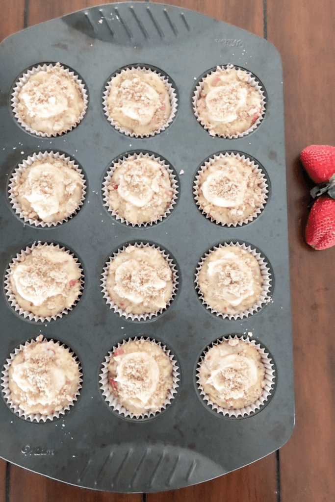 Muffin batter placed in muffin tins, ready to place in the oven, with fresh strawberries beside it