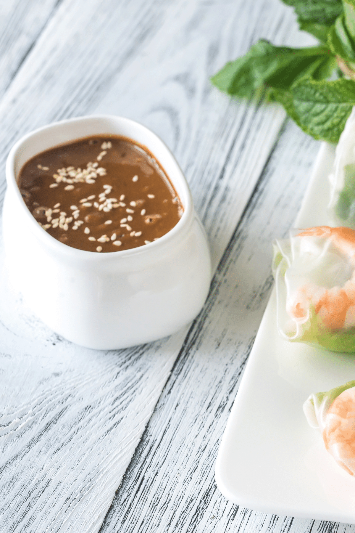 dipping sauce for rice paper rolls with sesame seeds sprinkled on top